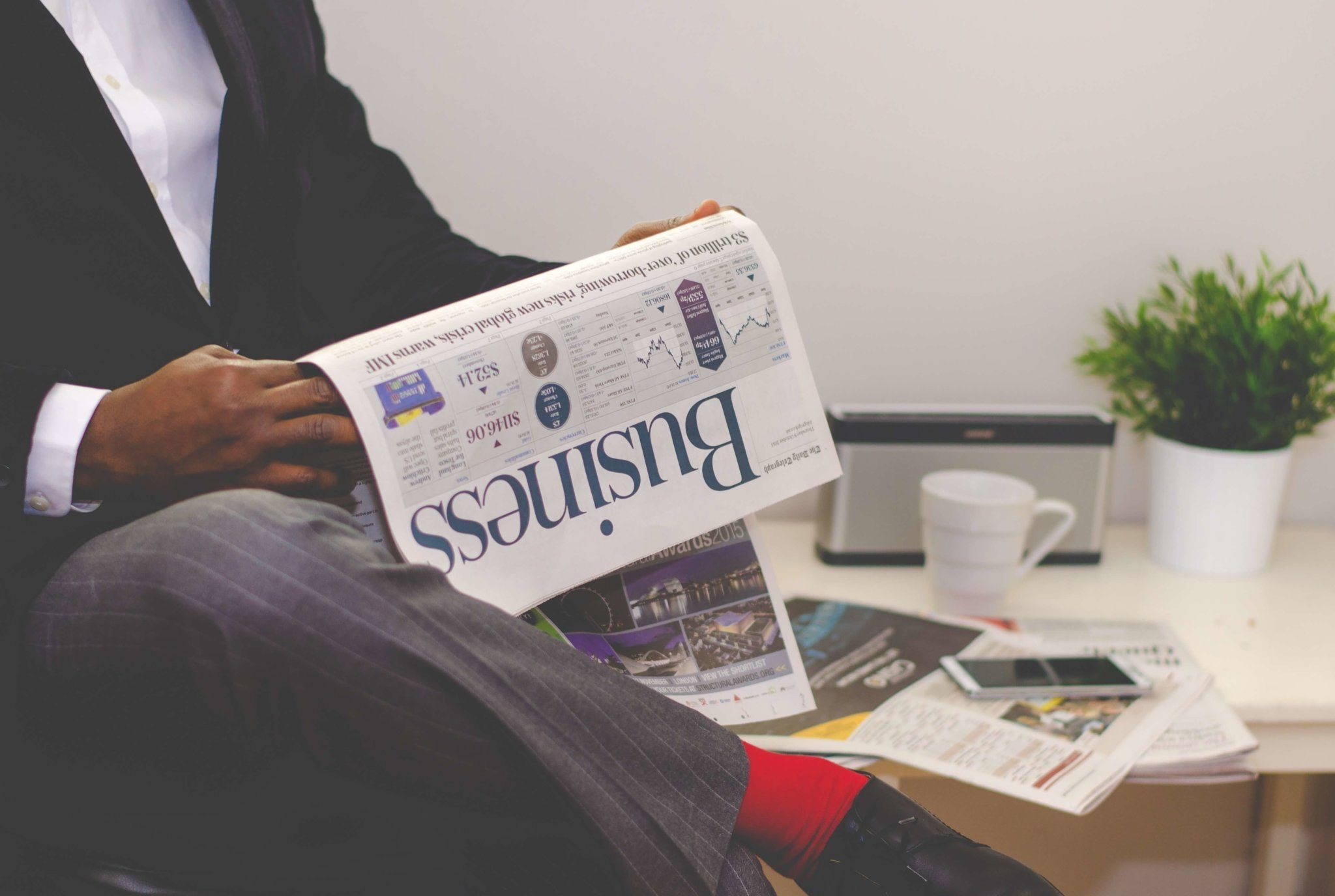 A person reading a business newspaper for successful change management.
